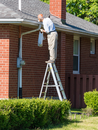 Seniors in Canada: Senior man cleaning a rain gutter on a ladder. Clearing autumn gutter blocked with leaves by hand. 에디토리얼