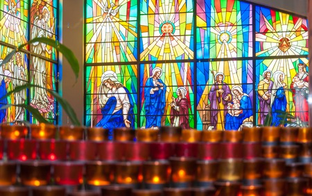 angel gabriel: Inside details of Annunciation Catholic Church.  Colorful Stained glass windows depict scenes from the Bible for in Toronto.  Red candles glow at the bottom of the frame. Editorial