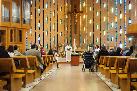 congregation: Inside details of Annunciation Catholic Church.  Sunlight filters through stained glass windows over the wooden altar.  Several churchgoers line the wooden pews.