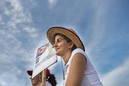 specifically: Scenes of Pope Francis to Havana, specifically the historic Catholic Mass held in the Revolution Square. Young lady holding a Papa Francisco sign. General public attending the religious mass.