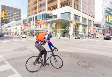 road cycling: Cyclist in downtown Toronto.  The man wears a blue shirt, orange bag, and blue pants as he rides his bicyle down a city street.  Several steel and glass buildings and some cars and pedestrians can be seen in the background.