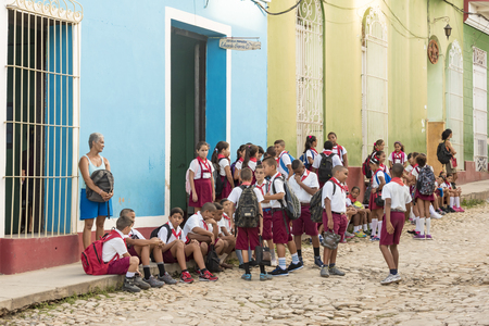 pioneers: Trinidad de Cuba scenes: Cuban pioneers or children outside a school in the morning waiting for the signal to enter classes.