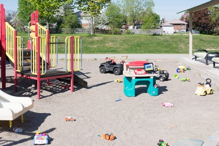 place for children: Childrens play area at a park. Toys all over the place in a sand-filled play area with slide and railed walk-way for children. Stock Photo