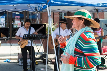 ave: An old lady dancing at the Salsa on St. Clair Ave West with a band of musicians playing music in the background. The lady is seen wearing a hat and the musicians are playing the guitar. Salsa on St. Clair Ave West is Torontos biggest celebration of salsa