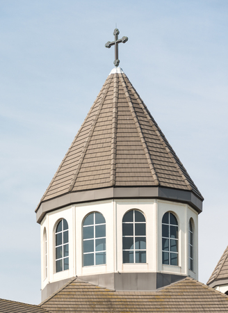 cone shaped: Closeup of the spire of a church with a cross on the top, against a clear blue sky. It is cone shaped structure pointing upwards, with brown tiles on it.