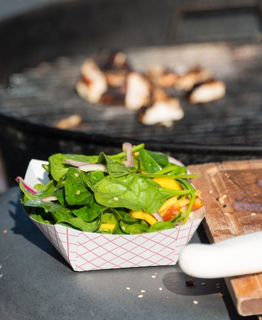 faintly visible: Scenes from Taste of Little Italy festival. Closeup of a bowl full of spinach leaves, chopped onions and yellow capsicum. A barbecue grill is faintly visible in the background, Taste of Little Italy festival on College Street is a bustling annual street f