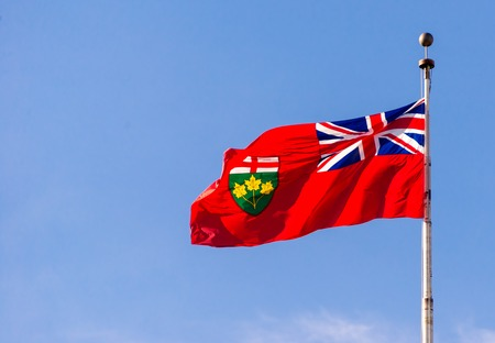 Flag of Ontario flying high on a flag post, against blue sky. The flag is a defaced Red Ensign, with the United Kingdoms Union Flag in the canton and the Ontario shield of arms in the fly.