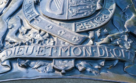 motto: Metal emblem of the Royal coat of arms of the United Kingdom having the motto Dieu et Mon Droit. Dieu et Mon Droit is the motto of the Monarch of the United Kingdom outside of Scotland which in French means God and my Right.