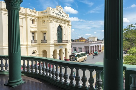 balcony: Spanish Colonial architecture in Cuba: Teatro La Caridad in Santa Clara, Cuba. The monument is a colonial theatre built in 1885. It is a National Monument of Cuba. View of Teatro La Caridad from the balcony of an adjacent building with railings in the for