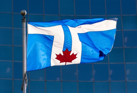 suggests: Flag of Toronto city. The flag displays twin towers of the Toronto City Hall on a blue background, with the red maple leaf at its base representing the Council Chamber at the base of the towers. The shape of the space above and between the towers suggests