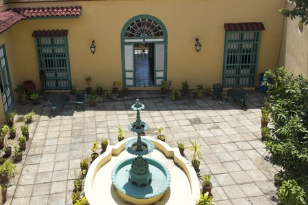 fled: Museo de Arte Colonial, Sancti Spiritus, Cuba. Antique fountain placed in the centre of an open space at the museum.  The museum is the opulent former palatial mansion of the Valle Iznaga clan, one of Cubas most elite families who fled Cuba after Fidels Editorial