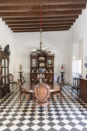 reloj de pendulo: El salón comedor en el Museo de Arte Colonial, Sancti Spiritus, Cuba. Mesa de comedor de madera, armarios para el almacenamiento de vajilla y reloj de péndulo que pertenece a los propietarios de la mansión en la exhibición. El museo es la antigua mansión palaciega opulenta del Valle Izn