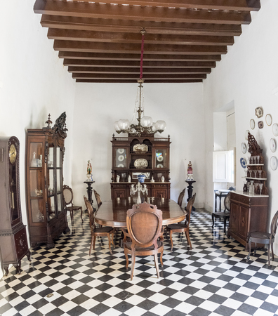 palatial: The Dining hall at Museo de Arte Colonial, Sancti Spiritus, Cuba. Wooden dining table, cupboards for storing crockery and pendulum clock belonging to the owners of the mansion on display.  The museum is the opulent former palatial mansion of the Valle Izn