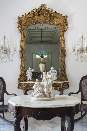 fled: Museo de Arte Colonial, Sancti Spiritus, Cuba. Antique wooden table with a marble top and a large bronze framed mirror on the wall.  The museum is the opulent former palatial mansion of the Valle Iznaga clan, one of Cubas most elite families who fled Cub