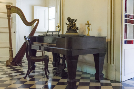 palatial: Music room at Museo de Arte Colonial, Sancti Spiritus, Cuba. Antique piano and a harp used by the mansion owners on display.  The museum is the opulent former palatial mansion of the Valle Iznaga clan, one of Cubas most elite families who fled Cuba after Editorial