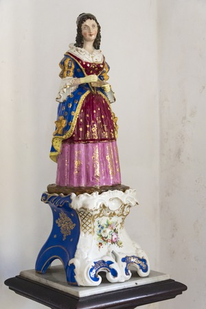palatial: Articles at Museo de Arte Colonial, Sancti Spiritus, Cuba. Small painted statue of a woman in royal clothing.  The museum is the opulent former palatial mansion of the Valle Iznaga clan, one of Cubas most elite families who fled Cuba after Fidels Revo