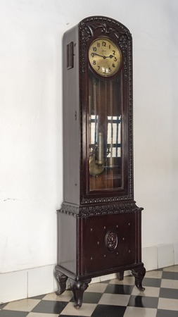 fled: Articles at Museo de Arte Colonial, Sancti Spiritus, Cuba. Antique wooden pendulum case clock on display.  The museum is the opulent former palatial mansion of the Valle Iznaga clan, one of Cubas most elite families who fled Cuba after Fidels Revolution