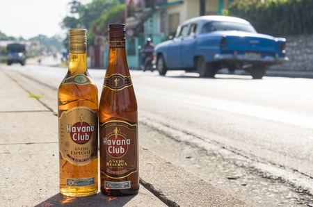 cuban culture: El Ron de Cuba: Bottles of Havana Club rum on the pavement with vehicles moving in the background.  Havana Club brand of rum created in 1934, is one of the best-selling rum brands in the world and also promotes Cuban culture across the globe.