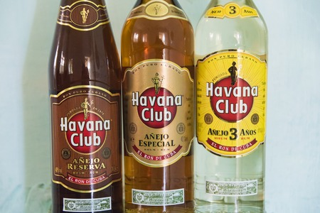 promotes: El Ron de Cuba: Closeup of three varieties of Havana Club rum bottles.  Havana Club brand of rum created in 1934, is one of the best-selling rum brands in the world and also promotes Cuban culture across the globe..