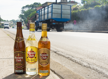 ron: El Ron de Cuba: Bottles of Havana Club rum on the pavement with vehicles moving in the background.  Havana Club brand of rum created in 1934, is one of the best-selling rum brands in the world and also promotes Cuban culture across the globe.
