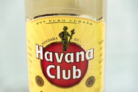 promotes: El Ron de Cuba: Closeup of a Havana Club rum bottle.  Havana Club brand of rum created in 1934, is one of the best-selling rum brands in the world and also promotes Cuban culture across the globe..