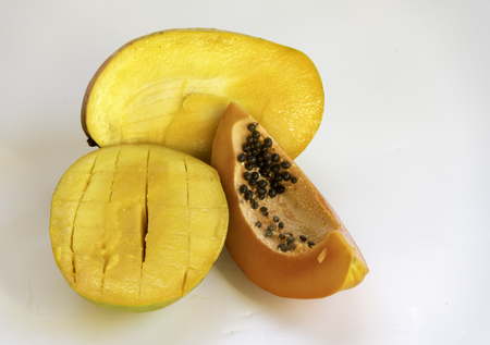 cutaneous: Tropical mango fruit cut into two pieces along with a slice of ripe papaya on white background.