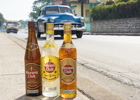El Ron de Cuba: Bottles of Havana Club rum on the pavement with vehicles moving in the background.  Havana Club brand of rum created in 1934, is one of the best-selling rum brands in the world and also promotes Cuban culture across the globe.