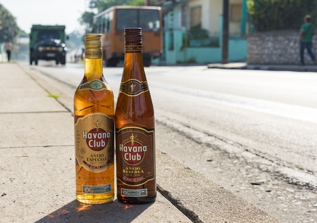 alcoholic drink: El Ron de Cuba: Bottles of Havana Club rum on the pavement with vehicles moving in the background.  Havana Club brand of rum created in 1934, is one of the best-selling rum brands in the world and also promotes Cuban culture across the globe.
