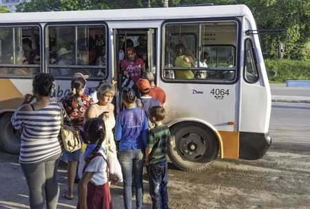 overcrowded: Cuba news: Everyday transportation or commuting: Passengers standing in line to board an overcrowded omnibus in Cuba.