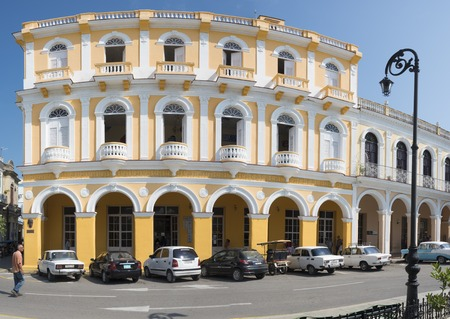 colonial building: Cuba tourism: Hotel Perla de Cuba at the Serafin Sanchez Park. The hotel has oval and rectangular balconies with magnificent arches. Cars parked in front of the hotel.  The colonial building is made in eclectic architecture and is a major tourist attracti