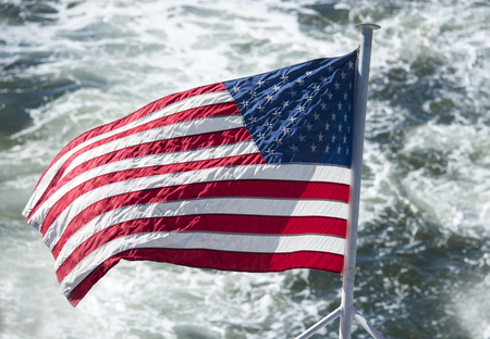 hudson river: United States of America flag flying or waving in boat or cruise in the Hudson River.  Beautiful symbol of freedom in New York city. Stock Photo