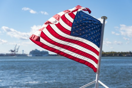United States of America flag flying or waving in boat or cruise in the Hudson River.  Beautiful symbol of freedom in New York city. Stock Photo