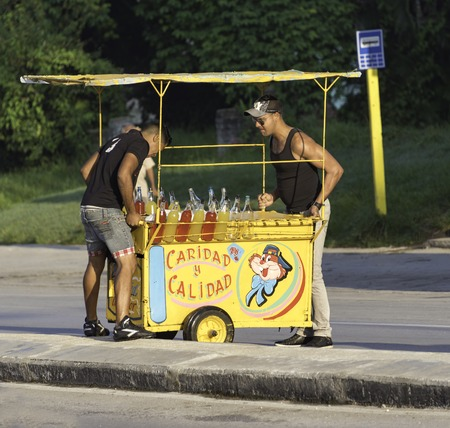 Push cart vendors in Cuba: Two men lifting a pushcart onto the road median. There are colorful bottles of local made juices and soft drinks in the cart.