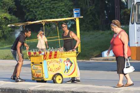 median: Push cart vendors in Cuba: Two men lifting a pushcart onto the road median. There are colorful bottles of local made juices and soft drinks in the cart.