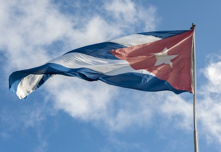 cuban flag: The Cuban flag flying high against a cloudy blue sky.  The flag of Cuba consists of five blue and white alternating stripes, and a red equilateral triangle at the hoist with a white five-pointed star.
