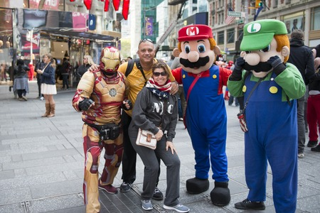 mario: Tourists with video game characters Mario and Luigi posing for photograph in New York. Couple having fun with cartoon characters at a market street in New York.