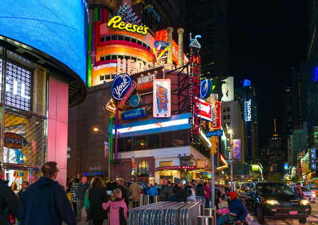 new york times: New York Times Square night scenes featuring the crowd and neon ads. The tourist landmark is visited by about 50 million tourists every year and is famous for counting down to the new year each year.