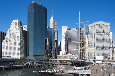 bot: Ships of South Street Seaport Museum: Historic ships Pioneer, and the Peking docked at Manhattan harbor, New York City. The Manhattan cityscape in the background.  The Peking is a steel-hulled four-masted barque and Pioneer is an 1885 built schooner , bot