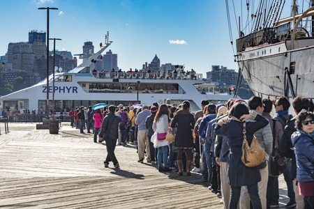 Tourism in New York: Tourists at the South Street Seaport standing in line beside the historic ship Peking. The Zephyr Seaport Liberty Cruise is also seen.  The South Street Seaport museum has 6 ships on display which takes tourist around the New York har Editorial