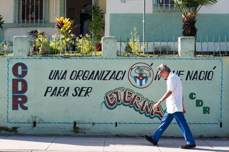 Cuba news: Revolutionary propaganda, CDR consign stating the organization is eternal. Senior passing in front of the sign.
