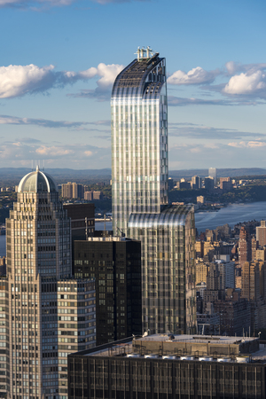 characteristic: New York landmarks and attractions: One57 building with its characteristic curved top as seen from the Rock Observation Deck.  One57, formerly known as Carnegie 57 is a supertall skyscraper in the Midtown neighborhood of Manhattan, New York City.