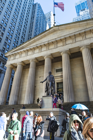 george washington statue: Tourists at Federal Hall National Memorial in New York city, USA with statue of George Washington in front.    Federal Hall National Memorial was built in 1842 as the United States Custom House. It is now operated by the National Park Service as a nationa
