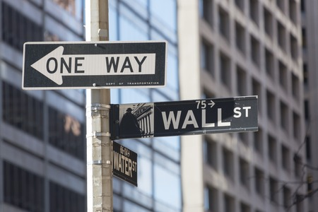 New York city navigation: Wall street signboard with Water street and one way signboards fixed on a pole at a traffic intersection in New York city, USA.  Wall Street is a 1.1 km street from Broadway to South Street on the East River in the Financial Dist