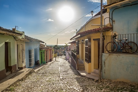 depict: Trinidad de Cuba scenes: Colorful houses along a cobbled street. The houses depict the colonial architecture and culture in Cuba.