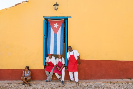 cuban culture: Trinidad de Cuba scenes: Restaurant La Botija workers posing for photograph with Cuban flag tied to the door.  Taberna La Botija is a private restaurant or paladar in Trinidad. The restaurant features a whole colonial decoration themed in the slavary in C