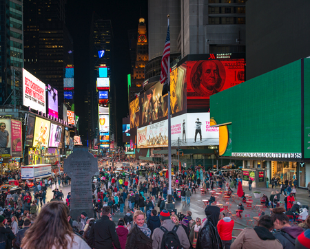 new york city times square: Times Square at night in New York City : Times Square is a major commercial intersection and neighborhood in Midtown Manhattan.The landmark is brightly adorned with billboards and advertisements.  Times Square is sometimes referred to as The Crossroads of