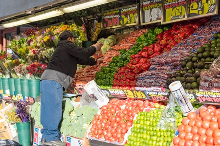 Mexican immigrant working arranging fruit in a convenience store in New York city. Beautifully arranged display of fruits and other produce wiht handpainted signs in the Historic District of New York City