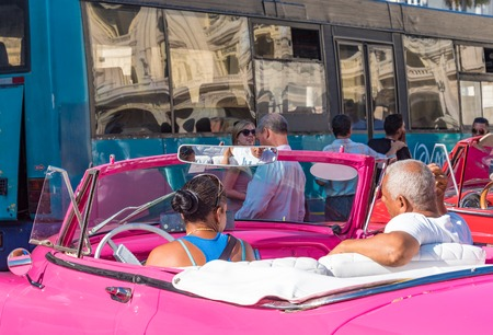 buen vivir: Cuban woman driving classic old American car. Vintage cars are a major attraction in Cuba and a good way to make a living by driving tourists around.
