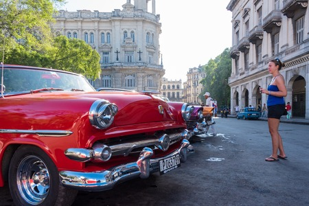 everyday: Cuba tourism: old vintage classic American cars in Havana and the Cuban everyday lifestyle. Tourist taking photos of the vehicles taxi  Cuba transportation scenes are a major tourist attraction. Having a great collection of vintage cars, Cuba is profiting