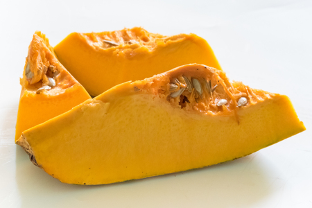 expensive food: Expensive food Cubans buy: Slices of raw pumpkin in bright yellow color placed against white background.  The low efficient agricultural industry in Cuba necessitates import of food produce which means higher prices. Stock Photo